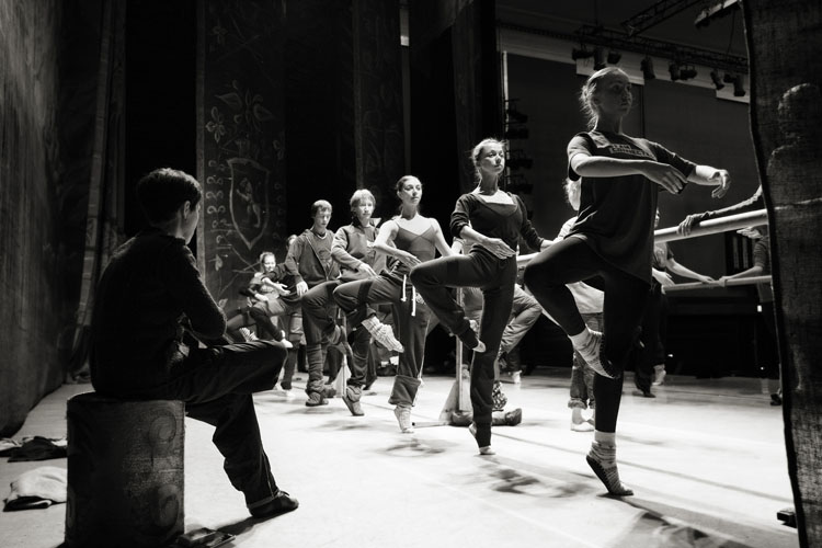 A black and white image of ballerinas at the barre on stage at The Colosseum in Watford