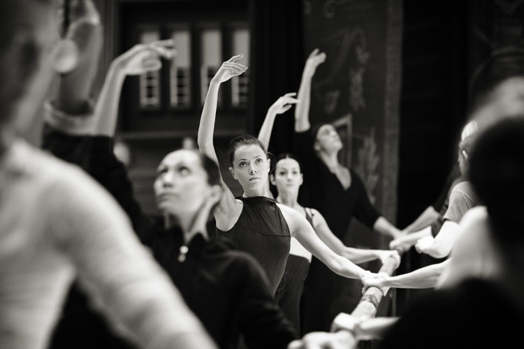 A black and white photograph of ballet dancers warming up by Helen Maybanks