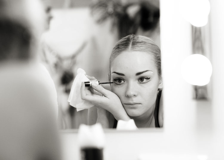 A ballerina from the Russian State Ballet of Siberia applying her make-up in the mirror