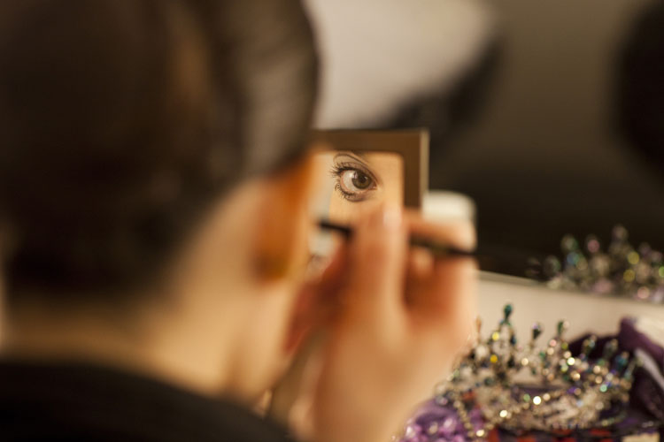 A ballerina applying her make-up in the mirror, backstage at The Colosseum in Watford