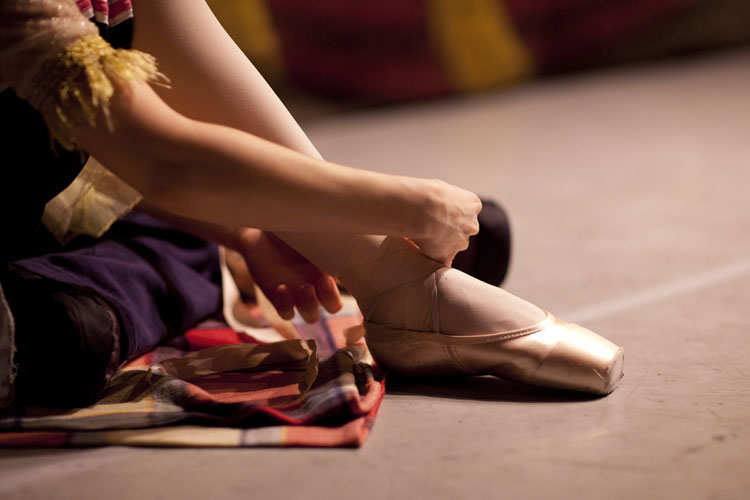 A ballerina from the Russian State Ballet of Siberia doing up her shoes. Copyright Helen Maybanks 2011
