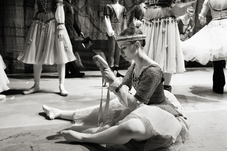 A balerina checking her pointe shoes before going on stage at the Watford Colosseum