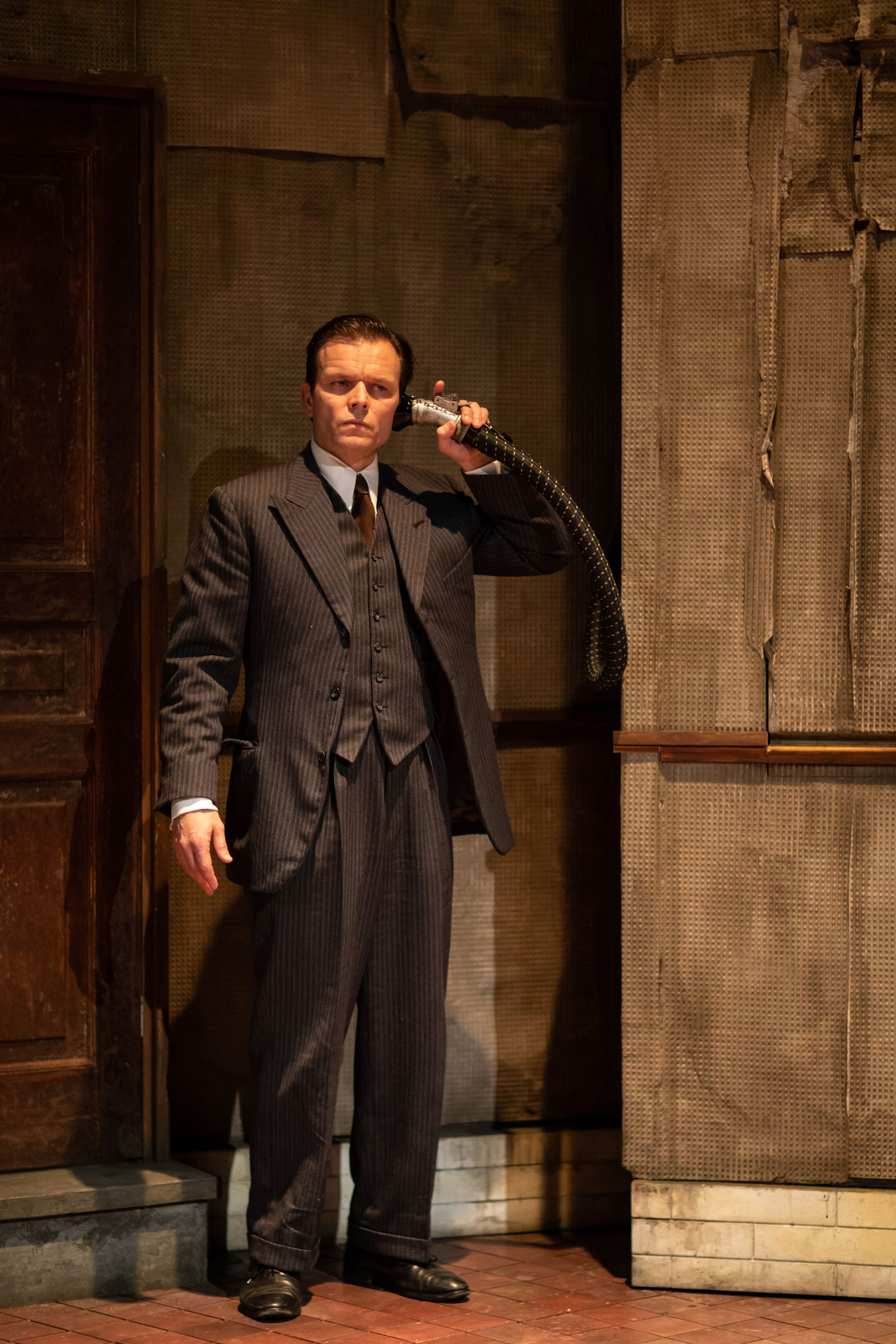 Alec Newman as Ben, listening to the voicepipe of the dumb waiter